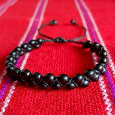 • Achira Seeds Bracelet • ❌PLEASE DON'T BUY THIS LISTING❌ I will create a new listing! (DISCOUNT on BUNDLE) Handcrafted bracelet by Peruvian artisans.   Material: Black WAXED thread intertwined with Achira seeds from South Amreica & has an adjustable clasp!                                                ⓢⓘⓩⓔ: Fits up to 10 inches. ⚠️Due to the Huayruro seed's delicate properties please avoid exposure to water ⚠️ Jewelry Bracelets