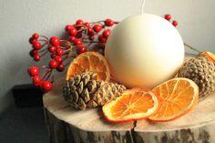 Centrotavola Natalizio avente come base la sezione di un tronco e come decorazioni vere pigne e vere arance essiccate