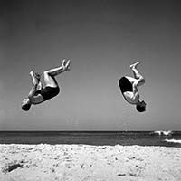 A flash bulb on George's camera has frozen the twin backflips by these two gymnasts mid-air and illuminated the sand suspended beneath them. This ability to anticipate and compose a fleeting moment is a measure of his photographic skill. Although front somersaults are easier to learn, backward somersaults are easier to perfect, as the tumbler can see their landing and correct body rotation. 4 October 1936