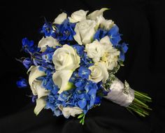 Beautiful Dutch blue hydrangea, white roses, white calla lilies, white spray roses and deep blue delphinium bouquet with a crystal butterfly keepsake brooch.