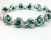 This half Persian weave design would accommodate a larger bead size or vs especially if a tiny single jump ring were in between each section. Although I would not alternate the V Direction. Chainmaille Bracelet, Beaded Bracelets, Crystal Beads, Crystals, Faceted Glass, Gemstone Jewelry, Handmade Jewelry, Gemstones, Persian