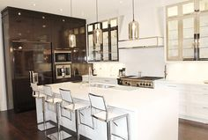 High gloss stained walnut cabinetry mixed with painted white and chrome throughout the kitchen makes this kitchen unique www.cmidesign.ca #CMID