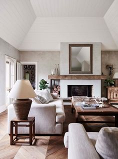 Living room with reclaimed timber floorboards, a fireplace with an oak mantle and sofas from Coco Republic | Photography: Lisa Cohen | Styling: Beck Simon