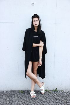 Elisa from www.schwarzersamt.com is wearing a all black look with white Birkenstocks arizona. She is wearing a high waist jeans shorts from Weekday, a black trench coat and a golden casio watch