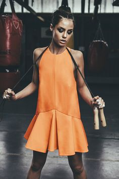 Sportswear inspired orange dress, complete with box pleats and no shoulder seams.