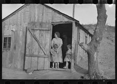 Mrs. Earl and her children in the doorway of their home.  Earl had constructed the house to withstand the big Midwest wind and weather, so the only way to get some breeze in the house was to open the front door.