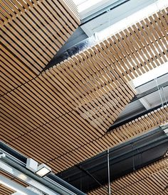 A conversion of an early 20th century barn features an intricate custom-made solid wood feature grill panel ceiling, bespoke designed by the expert Hunter Douglas team.