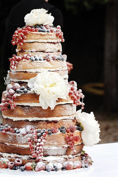 A beautiful naked wedding cake with seasonal berries & flowers