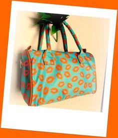 Bolsa de mão feita em tecido cetim fosco com estampa de beijos. Possui alça para usar transpassada. R$68,00