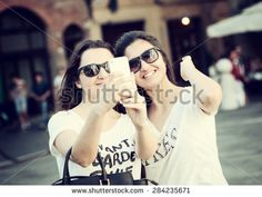 Two young women with sunglasses taking a selfie with the smart phone