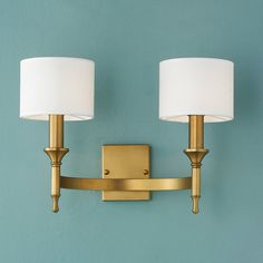 "Half circle arm bracket and 2 torch candlelights give this wall sconce metropolitan chic style. Aged Brass or Polished Nickel with drum shades (included). 2x40 watts. (13""Hx18""Wx11""D)    Backplate: 4.3""Wx5.12""H."
