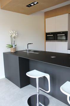 Moderne strakke keuken, wit en zwart gecombineerd met hout. Kookeiland in materiaal Fenix NTM Negro Indigo, extreem mat!