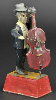 """MAN PLAYING BASS GUITAR Germany, Gunthermann, whimsical depiction of standing figure holding bass and bow in hand, able to emit sound when clockwork is activated, great action. 10"""" h. Some flaking to paint, (VG Cond.)"""
