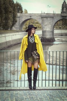 A yellow trenchcoat and olive silk shorts will showcase your sartorial self. Black leather over the knee boots are a savvy choice to complete the look.  Shop this look for $217:  http://lookastic.com/women/looks/hat-trenchcoat-over-the-knee-boots-necklace-crew-neck-sweater-clutch-shorts/4834  — Black Wool Hat  — Yellow Trenchcoat  — Black Leather Over The Knee Boots  — Silver Necklace  — Olive Crew-neck Sweater  — Tan Leopard Suede Clutch  — Olive Silk Shorts