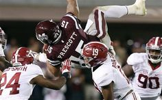 Mississippi State quarterback Dak Prescott (15) is upended by Alabama's defense during the second half of a game in Starkville, Nov. 14, 2015. Prescott was sacked 9 times on the day.