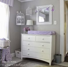 Girl's nursery in gray and lavender with hanging birdcages.