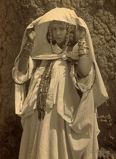 Woman of Ouled Nail, wearing coin necklace, bracelets, and other jewelry. Algeria. 1860-1890