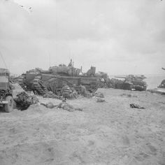 Medics attending to wounded in the lee of a Churchill AVRE from 5th Assault Regiment, Royal Engineers, on Queen beach, Sword area. (June 6, 1944). Source: Imperial War Museums, # B 5095.