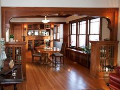DINING ROOM, AFTER: A new neutral wall color allows the emphasis to fall on the aged quarter-sawn oak, and the hardwoods floors only needed to be sanded and refinished to look new again.
