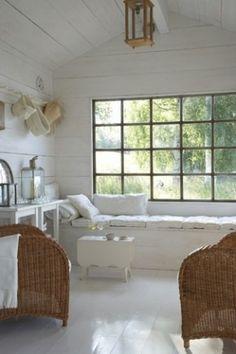 Wit houten tuinhuis met raambank voor groot raam met uitzicht op de tuin.