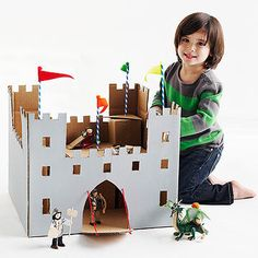 Cut notches along the top of an extra-large box to make a cardboard castle. Add tiny knights and toy horses for hours of play. The only thing missing from this fantastic fortress is a moat.                 What you'll need: 20x20x20-inch box, scissors, ruler, pencil, X-Acto knife, cutting mat, hot-glue gun, gray acrylic or tempera paint, paintbrush, 2 or 3 small cardboard boxes, red string, chenille stems, striped drinking straws, small pom-poms, felt                 Make it: While box is…