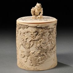Ivory Covered Box, Japan, 19th/20th century, tubular, depicting in bas-relief a brouhaha with various onis and mythical animal-headed creatures, the cover incised with floral scrolls and surmounted with a yokai-shaped finial, ht. 8, dia. 5 1/8 in.