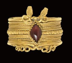 A GREEK GOLD AND GARNET FINGER RING   HELLENISTIC PERIOD, CIRCA 3RD CENTURY B.C.  In the form of two serpents...