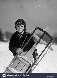 2a3b6fd5b Stock Photo - 1920s 1930s SMILING BOY WEARING AVIATOR GOGGLES LEATHER  FLYING HELMET HOLDING SLED STANDING IN SNOW FIELD LOOKING AT CAMERA