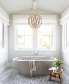 A gray stone oval bathtub sits on a gray prism floor tiles beneath a rope chande… - Modern Ux Design, House Design, Concrete Bathtub, Stone Bathtub, Concrete Interiors, Bath Decor, White Bathroom, Spa Master Bathroom, Bathroom Marble