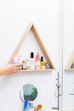 Use a uniquely shaped shelf to store everyday items. Click through for the full reveal of this minimal modern bathroom makeover.
