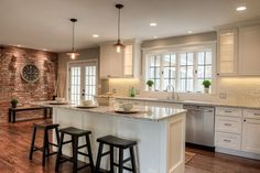 shaker white cabinets in small open kitchen with wide-plank oak floors, brick wall and mullion windows and glass cabinets lit from inside