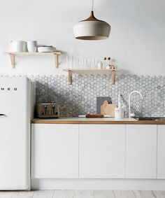 A backsplash of hexagonal Carrara marble from Australia's Di Lorenzo Tile offsets the minimalist cabinetry in this kitchen styled by Jackie Brown.