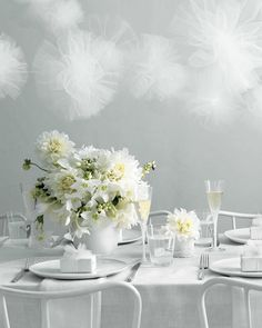Strings of gauzy tulle pom-poms float above a whitewashed landscape, creating a dreamy, light-as-air effect. To ground the scene and add interest to a pure white palette, incorporate plenty of texture. Here, we chose a raw linen tablecloth, net fabric runner, lace-pattern porcelain vase, and a mix of sleek and gardeny blooms, including Eucharis lilies and dinner-plate dahlias.