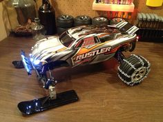 My Traxxas Rustler XL5 - front snow skis, rear chains, and LED lights.