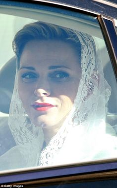 Princess Charlene appears to smile at well-wishers from her car following the state visit with the pope