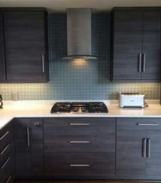 """Grey Wenge Wood Cabinetry wirh Modern Hood, and 2"""" square Seafoam Green Glass Tiles on the Backsplash..."""