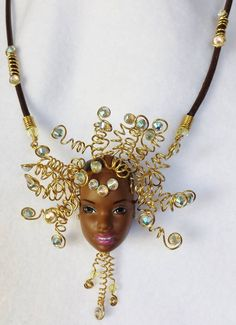 Nefertiri, Queen of Egypt (Barbie head) made of non-tarnish brass with swarovski crystals on leather.  First of the Omigawd Becky necklaces.  SOLD  Gilding the Lily by Candace Eck.