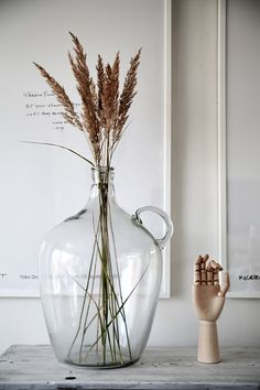 Home decor details - a rustic wood tabletop styled with a large glass jug and dried grasses, a wood hand, and large white framed typography art. Living Room Sets, Rugs In Living Room, Interior Styling, Interior Design, Interior Plants, Glass Jug, Glass Desk, Wood Glass, Vases Decor