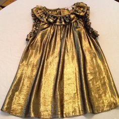 Hunter Dixon gold shimmery sleeveless top. Hunter Dixon gold shimmery sleeveless top. Ruffled neckline and sleeves. (Hunter Dixon's clothing line is now Hunter Bell) Tops