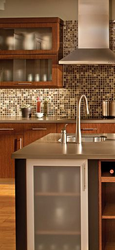 Contemporary Kitchen by Dura Supreme - The aluminum framed accent doors and the stainless steel hood provide industrial flavor.  Tile up to cabinet height! Like this for our kitchen