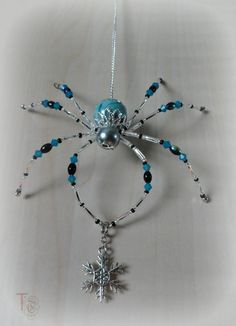 SOLD - I have many other beautiful spiders available in my shop, or I can make you one similar to Stormy; Christmas Spider Legend  Stormy is a gorgeous 4x4 inch beaded Christmas spider that shimmers and shines and cant wait to be part of your home décor. The blue and black crystals and beads are just like the blue skies that give way to dark clouds and the silver glass bugle beads on her legs shimmer brightly like flashes of lightening. She is holding a beautiful silver snowflake charm that…