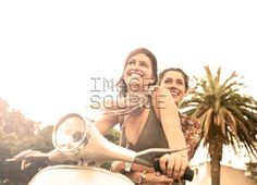 Two young female friends riding moped