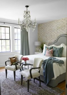 Soft elegant bedroom with beautiful chandelier and brick wall