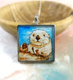 The Sea Otter --Watercolor Painting Necklace by Sarah-Lambert Cook... these little guys are so cute. They hold hands while they sleep so they don't drift apart!  http://www.sarahlambertcook.com/collections/necklaces/products/the-sea-otter-watercolor-painting-necklace