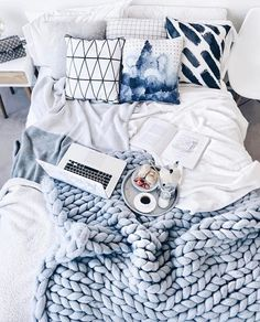 gorgeous bedroom in blue, white, and light gray with shibori indigo throw pillows and arm-knit blanket