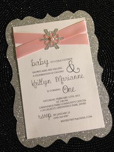 First Birthday Invitation designed in pink and silver, adorned with satin ribbon and a pretty snowflake.