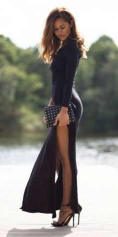 Sharareh Sophia Hosseini + high necked + tightly fitted maxi dress slit to the thigh + high black stiletto heels + studded clutch bag. Product information not available.