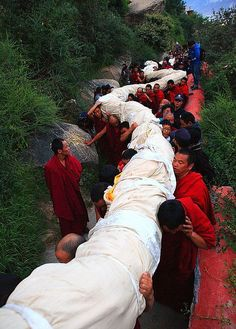 Tibetan monks are carrying a giant Thangka of Buddha uphill during the annual Shoton Festival. It is the best time to travel to Tibet to enjoy a big feast of Tibetan culture.