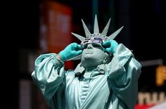 A man dressed as the Statue of Liberty watches a partial solar eclipse, New York City, US