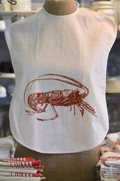 Protect your shirt from spills and splashes by wearing this bib-style apron.  Manufactured in South Africa Made from linen rich fabric Ties to secure around the neck Designed by and exclusive to Masquerade